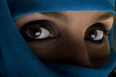 Woman with shawl on face. Young woman with face covered by blue shawl and shadow