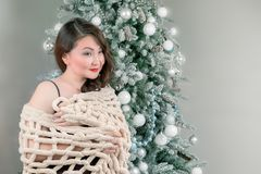 Woman in shawl near the christmas tree. Beautiful asian woman in shawl near the christmas tree with copy space Royalty Free Stock Photos