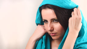 Woman with shawl over head. Beautiful young woman taking off blue shawl from around her face Royalty Free Stock Images