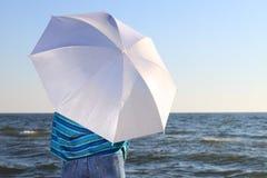 Woman and shawl at sea shore. Blue woman and parasol at sea shore Stock Images