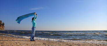 Woman and shawl at sea shore Stock Photos