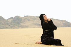 Woman in shawl sitting on sand looking up Stock Photo