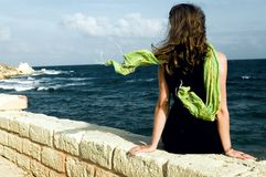 Woman with shawl, sitting on wall an looking at sea. Young woman looking at sea, shawl on the wind Royalty Free Stock Image