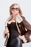 Woman in a sheepskin coat on a background blue sky Stock Photo
