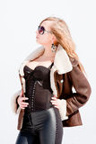 Woman in a sheepskin coat on a background blue sky Royalty Free Stock Image