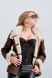 Woman in a sheepskin coat on a background blue sky Stock Photos