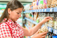 Woman on the shelf at the store chooses  nuts Royalty Free Stock Images