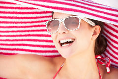 Woman Sheltering From Sun On Beach Holiday stock photo