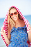 Woman Sheltering From Sun On Beach Holiday Stock Images