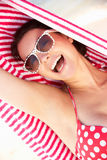 Woman Sheltering From Sun On Beach Holiday Stock Image