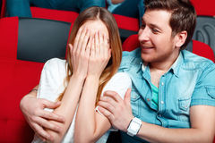 Woman shielding eyes with hands in cinema Stock Images