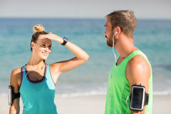 Woman shielding eyes while looking at man. Young woman shielding eyes while looking at man on shore during sunny day royalty free stock images