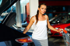 Woman shifts the purchase from shopping cart in the trunk of a c Stock Image