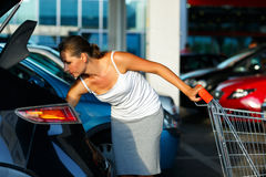 Woman shifts the purchase from shopping cart in the trunk of a c Stock Photography