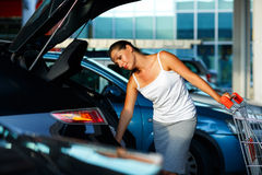 Woman shifts the purchase from shopping cart in the trunk of a c Stock Photo