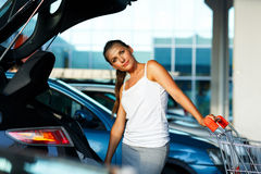 Woman shifts the purchase from shopping cart in the trunk of a c Royalty Free Stock Photography