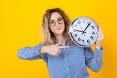 Woman in shirt with clocks. Portrait of attractive curly-haired woman in striped shirt and round eyeglasses isolated on orange background holding clocks and stock photography