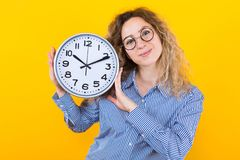 Woman in shirt with clocks. Portrait of attractive curly-haired woman in striped shirt and round eyeglasses isolated on orange background holding clocks time royalty free stock image