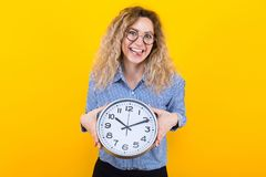 Woman in shirt with clocks. Portrait of happy curly-haired woman in striped shirt and round eyeglasses isolated on orange background holding clocks and showing stock photo
