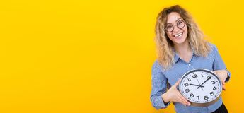 Woman in shirt with clocks. Portrait of smiling curly-haired woman in striped shirt and round eyeglasses isolated on orange background with copyspace holding royalty free stock photography