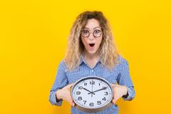 Woman in shirt with clocks. Portrait of surprised curly-haired woman in striped shirt and round eyeglasses isolated on orange background holding clocks time stock photo
