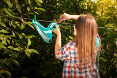 Woman in shirt drying bikini on clothesline Royalty Free Stock Photography