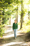 Woman in shirt and jeans walking in forest at sunny day Stock Photos