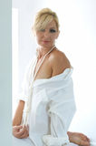 Woman with shirt off shoulder. An attractive blonde woman is wearing a man's dress shirt and her shoulder is exposed Stock Photography