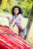 Woman in shirt posing on retro car side Stock Photography