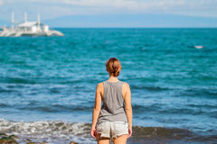 Woman in shirt and shorts on beach. Bright photo of young girl watching cruise boat. Royalty Free Stock Images