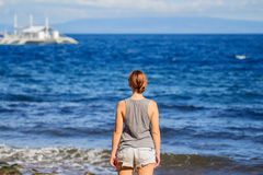 Woman in shirt and shorts on beach. Vibrant photo of young girl watching cruise boat. Royalty Free Stock Photos