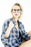 Woman in shirt sitting in bed and holding glasses to her face stock photography