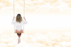 Woman with shirt and white pants on the swing through the clouds Stock Image