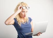 Woman in shock looking at laptop. Blonde woman in shock looking at laptop Stock Photo
