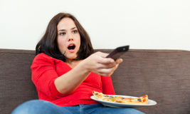 Woman shocked in front of television Royalty Free Stock Images