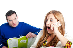 Woman shocked on the phone with man looking over Stock Image
