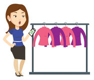 Woman shocked by price tag in clothing store. Stock Photography