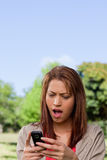 Woman with a shocked while reading a text message Royalty Free Stock Image