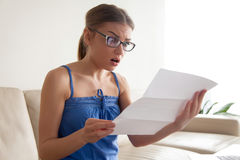 Woman shocked because of written notice from bank. Attractive young woman in eyeglasses feeling shocked because of written notice from bank, surprised with loan stock photography