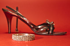 Woman shoe and diamond bracelet. Woman shoe and a bracelet on red background - wealthy Cinderella Royalty Free Stock Photo