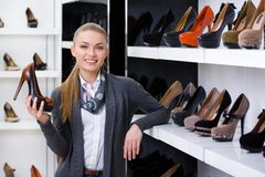 Woman with shoe in hand chooses high heeled shoes Royalty Free Stock Photography