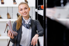 Woman with shoe in hand chooses shoes Stock Photography