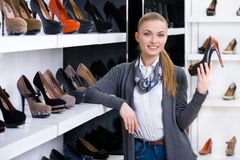 Woman with shoe in hand chooses stylish pumps. Looking at the shelves with numerous pumps Stock Image
