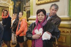Woman with shoe and hat. LUTSK, UKRAINE - 26 March 2017: Old woman holding baby shoe and hat in church during ceremony of christening Stock Photo