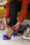 Woman in shoe shop. Woman is choosing shoes in shoe shop Royalty Free Stock Photo