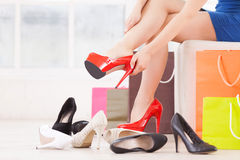 Woman at shoe store. Cropped image of young women choosing shoes in a shoe store Royalty Free Stock Photos