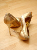 Woman shoes. Woman golden shoes on a wood floor Royalty Free Stock Image