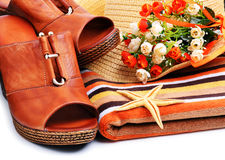 Woman shoes decorated with starfish, towels, beach hat Royalty Free Stock Photography