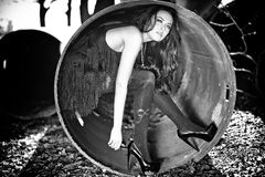 Woman in the shoes inside a metal pipe Stock Images