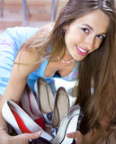 Woman with shoes in shopping mall. Happy woman shopaholic with heap of shoes in shopping mall stock photography